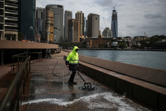 A worker cleans the mostly deserted waterfront area of the Sydney Opera House, in the wake of New South Wales implementing measures shutting down non-essential businesses and moving toward harsh penalties to enforce self-isolation as the spread of coronavirus disease (COVID-19). . REUTERS/Loren Elliott