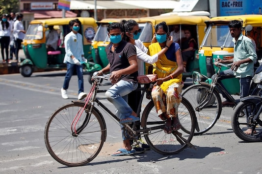 An NGO worker puts a face mask on a woman as a precaution against the spread of coronavirus, at a traffic junction in Ahmedabad. (REUTERS)