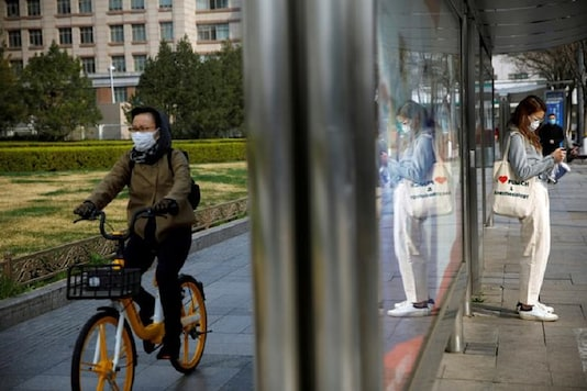 People wear face masks near a bus stop on a street following an outbreak of the coronavirus disease (COVID-19), in Beijing, China. (Reuters)