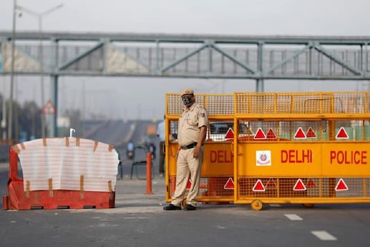 A police officer stands at New Delhi's border barricade during lockdown by the authorities to limit the spreading of coronavirus disease (COVID-19), in New Delhi