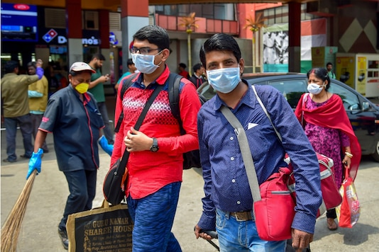 Commuters wears protective masks at a railway station in Bengaluru on Wednesday. (PTI)