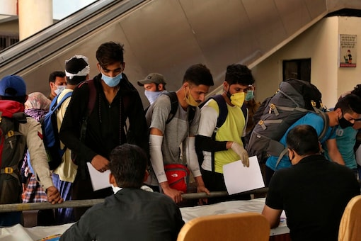 Commuters line up to get their temperature checked as a precautionary measure against a new virus in Jammu. (AP Photo)