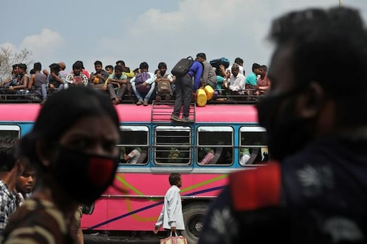 People board a crowded bus to return to their cities and villages in Kolkata on Monday. (Reuters)