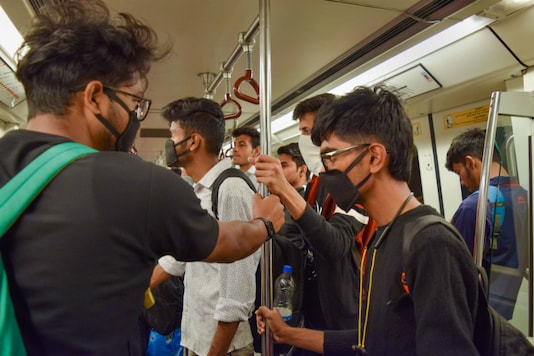 Passengers wear masks while travelling in a metro in New Delhi on Thursday. (PTI)