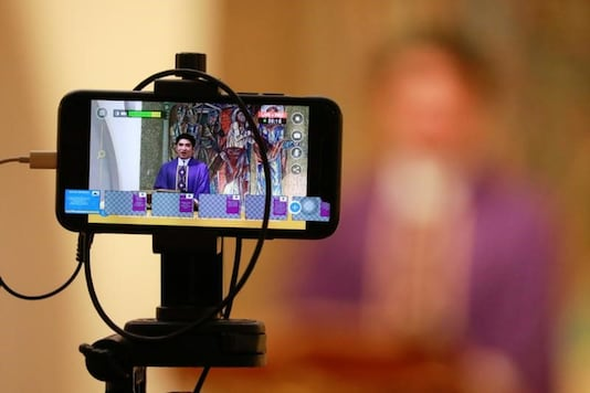 A priest celebrates mass live-streamed on Facebook following the suspension of mass gatherings due to the coronavirus outbreak, at an almost-empty chapel in Manila Cathedral in Manila, Philippines, March 15, 2020. REUTERS/Eloisa Lopez