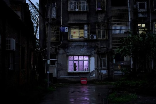 A man stands at a window at a residential community in Jingzhou, after the lockdown was eased in Hubei province, the epicenter of China's coronavirus disease (COVID-19) outbreak, March 26, 2020. REUTERS/Aly Song