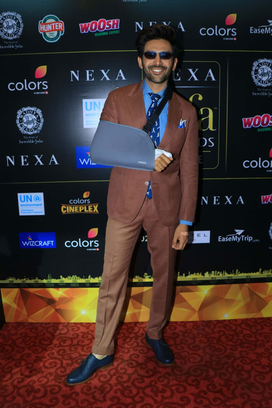 Bollywood star Kartik Aaryan, who underwent minor surgery earlier in the day, was seen heading to IIFA press conference with an arm sling. In this photo,Kartik is seen posing on the IIFA press conference red carpet. (Image: Viral Bhayani)