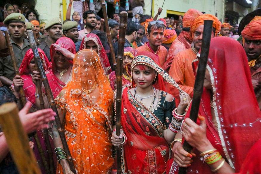 Women hold wooden sticks to beat men during the 'Lathmar Holi' festival, in Barsana. (Image: PTI)