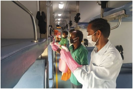A worker is seen cleaning train to prevent the AC virus from spreading. (Image: News18/ Ajay Kumar)