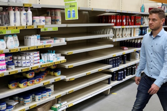 A shopper walks past an empty shelve of hand wash and hand sanitisers. Representative image.