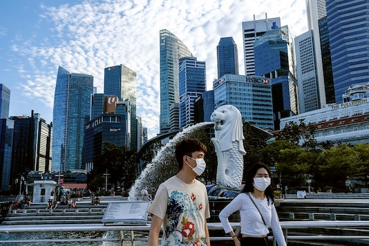 A couple wearing face masks walk past the Merlion statue in Singapore. (AP Photo)