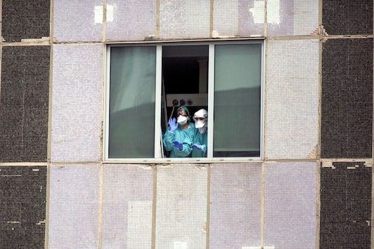Medical workers wearing face masks gesture from a hospital in Spain.  (AP Photo/Manu Fernandez, File)