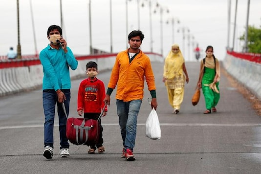 Sushil Kumar, a migrant worker, walks along a highway with his family to return to their village, during a 21-day nationwide lockdown to limit the spreading of coronavirus disease (COVID-19), in Gajraula, in the state of Uttar Pradesh, March 27, 2020. REUTERS/Adnan Abidi