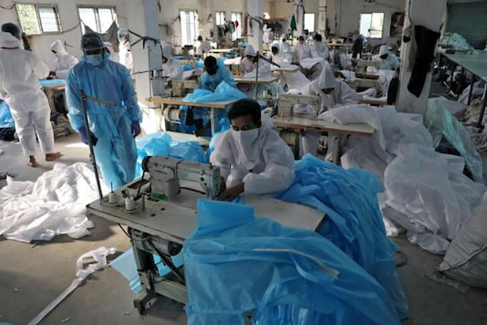 Representative Image. Workers stitch protective suits at a workshop before supplying them to a government-run hospital in Kolkata on Monday. (Reuters)