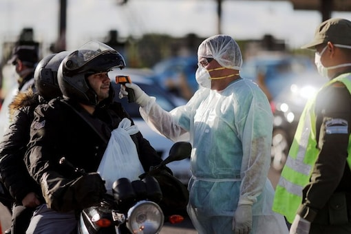 FILE PHOTO: A health worker takes the temperature of a driver for precaution due to coronavirus disease (COVID-19), in Buenos Aires, Argentina March 19, 2020. (REUTERS/Agustin Marcarian)
