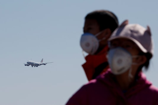 Representative Image. People wearing protective masks watch a plane of Air China land at Beijing Capital International in Beijing as the country is hit by an outbreak of the novel coronavirus in China. (Reuters)