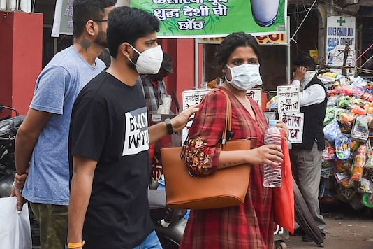 File photo: People wear protective masks in view of coronavirus pandemic at a market in Lucknow. (PTI)
