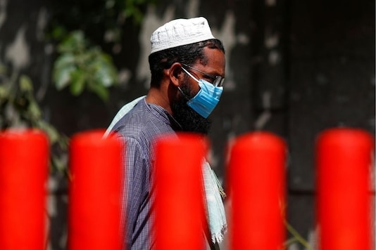 A man wearing a protective mask walks towards a bus that will take him to a quarantine facility, amid concerns about the spread of coronavirus disease (COVID-19), in the Nizamuddin area of New Delhi on Tuesday. (Reuters)