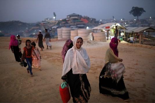 Rohingya refugees walk along the road in the evening at Balukhali camp in Cox's Bazar, Bangladesh.