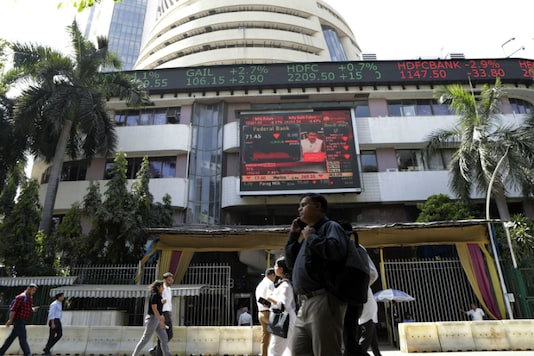 People walk past a display screen on the facade of the Bombay Stock Exchange in Mumbai on March 9, 2020. (AP Photo/Rajanish Kakade)