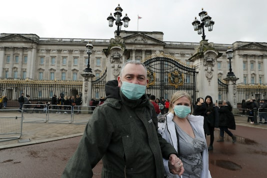 A couple wear face masks as they visit Buckingham Palace in London on March 14, 2020. (AP Photo/Frank Augstein)