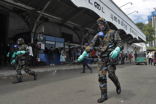 Sri Lankan government soldiers in protective clothes spray disinfectants in Colombo. (AP Photo/Eranga Jayawardena)