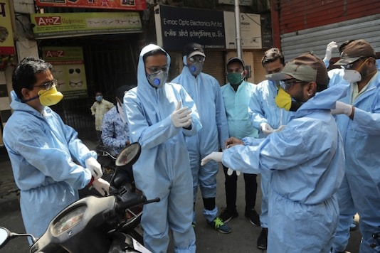 Members of a voluntary organisation wear protective gear before distributing food to people in Mumbai on March 29, 2020. (AP Photo/Rafiq Maqbool)