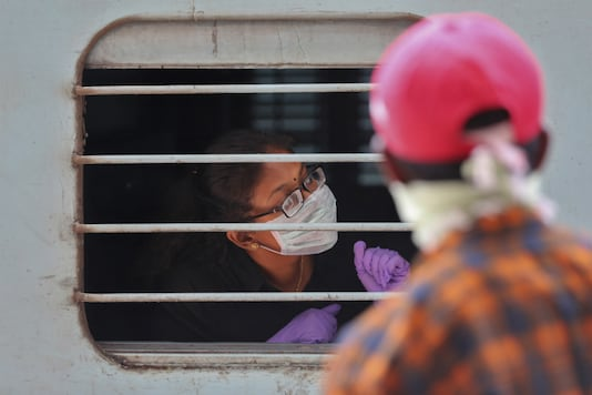 A passenger wearing face mask and gloves as a precaution against COVID-19 peeps out of a train window at Secunderabad Railway Station. (AP Photo/Mahesh Kumar A.)