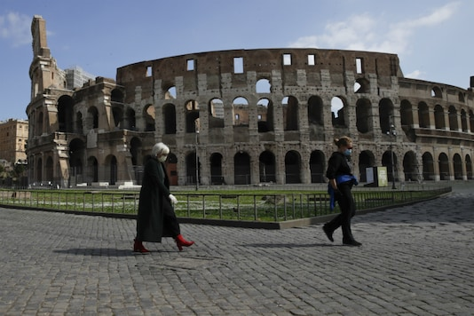 People walk past the Colosseum in Rome on March 15, 2020. (AP Photo/Alessandra Tarantino)