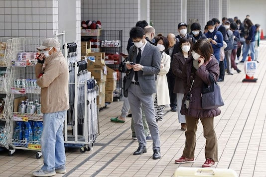 People wearing protective face masks following an outbreak of the coronavirus disease (COVID-19) queue as they wait for the opening of a drugstore in Tokyo, Japan March 27, 2020, in this photo taken by Kyodo. Mandatory credit Kyodo/via REUTERS