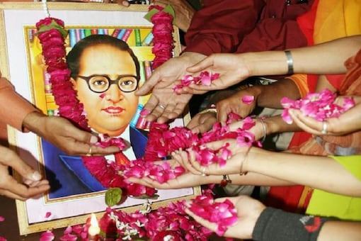 People scatter rose petals in front of a portrait of Dr. BR Ambedkar, the author of the Indian Constitution.