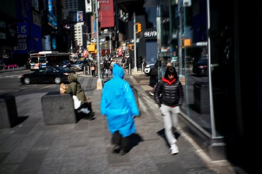 A man covered himself from the virus as people walk around Times Square as the coronavirus disease (Covid-19) outbreak continues in New York.  (REUTERS)