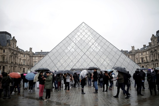 FILE PHOTO: Tourists queue to enter the Louvre as the staff closed the museum during a staff meeting about the coronavirus outbreak, in Paris, France, March 2, 2020. REUTERS/Benoit Tessier/File Photo