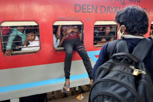 A migrant worker tries to board an overcrowded passenger train from an emergency window, after government imposed restrictions on public gatherings in attempts to prevent spread of coronavirus disease (COVID-19), in Mumbai on March 21, 2020. (REUTERS/Prashant Waydande)