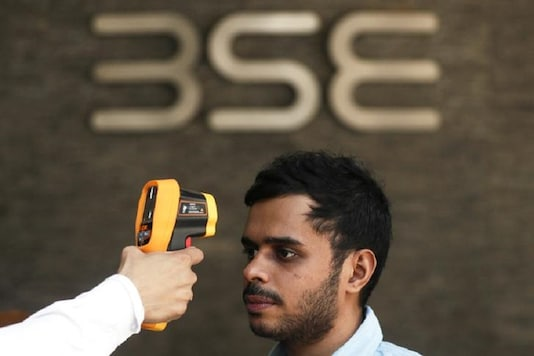 A security official scans a visitor with an infrared thermometer to check his temperature as a precautionary measure against coronavirus outside the Bombay Stock Exchange (BSE) in Mumbai. (Reuters)