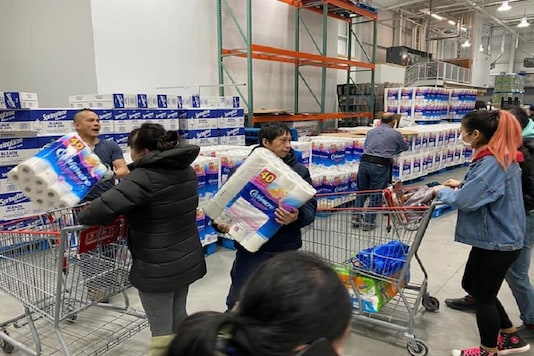 Workers ration toilet paper to one package per Costco member in an effort to stem hoarding due to fears of coronavirus, at a Costco store in Toronto, Ontario, Canada. (Reuters)