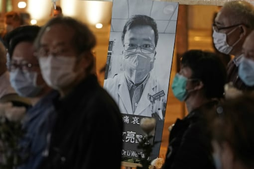 In this Feb. 7, 2020, file photo, people wearing masks attend a vigil for Chinese doctor Li Wenliang, who was reprimanded for warning about the outbreak of the new coronavirus, in Hong Kong. (AP Photo/Kin Cheung, File)