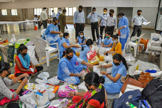 Surat Municipal Corporation members pack food to distribute among the poor during lockdown, in Surat on March 28, 2020. (PTI)