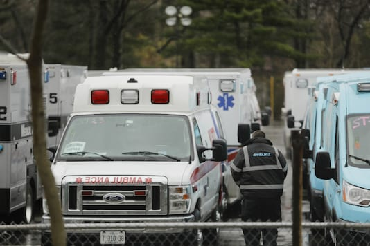 A man walks among ambulances parked at the Bronx Zoo during the coronavirus outbreak, on April 3, 2020, in the Bronx borough of New York. (AP Photo/Frank Franklin II)