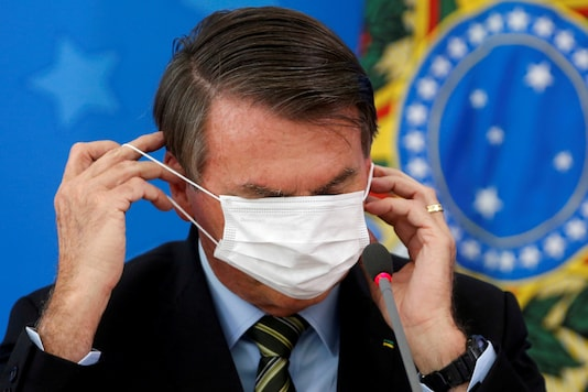 Brazil's Jair Bolsonaro adjusts his protective face mask during a news conference to announce measures to curb the spread of the coronavirus disease (COVID-19) in Brasilia, Brazil March 18, 2020. (REUTERS/Adriano Machado/File Photo)