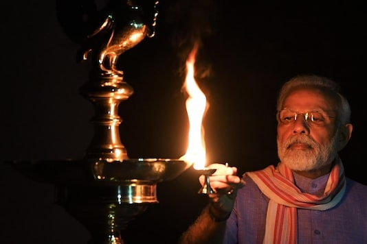 Prime Minister Narendra Modi lights a lamp on Sunday. (Image: Twitter)