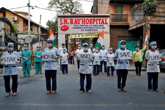 Medical staff members hold placards outside a hospital to show solidarity with people who are affected by the coronavirus disease in Kolkata. (REUTERS)