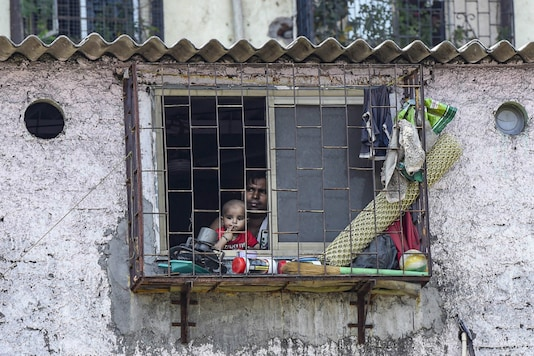 A man with his child looks through the window of his house during a nationwide lockdown in the wake of coronavirus pandemic, at Dharavi in Mumbai, on April 2, 2020. (PTI)