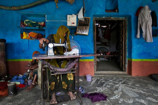 A woman works on a manual sewing machine inside her home at a village in Madhya Pradesh. (Reuters)