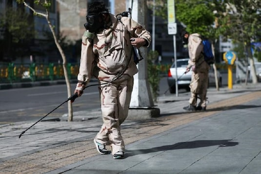 Volunteers from Basij forces wearing protective suits and face masks spray disinfectant on the streets, amid the coronavirus disease (COVID-19) fears, in Tehran, Iran April 3, 2020. WANA (West Asia News Agency)/Ali Khara via REUTERS