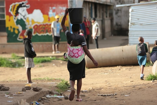 For representation: In this Monday, April 6, 2020 photo, a woman carries a her baby and a bucket of water in Harare. Lockdowns imposed to curb the coronavirus' spread have put millions of women in Africa, Asia and elsewhere out of reach of birth control and other sexual and reproductive health needs. (Image: AP)