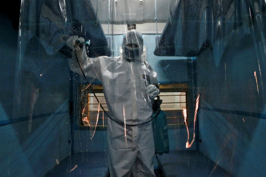 A worker wearing a protective suit disinfects the interior of a passenger train after it was converted into an isolation facility amid concerns about the spread of coronavirus disease (COVID-19), on the outskirts of Kolkata, on April 6, 2020. (REUTERS/Rupak De Chowdhuri)