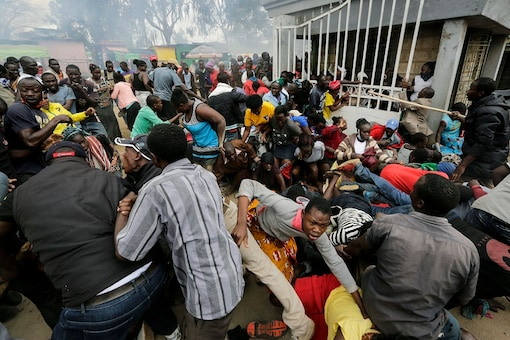 Residents of Kenya's Kibera slum, or informal settlement pushed through a gate for gaining access to food packets, which resulted in a stampede, causing police to fire tear gas, leaving several injured, at a district office in Nairobi on Friday. (AP Photo/Khalil Senosi)