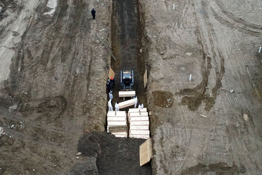 Workers wearing personal protective equipment bury bodies in a trench on Hart Island. (Image: AP)