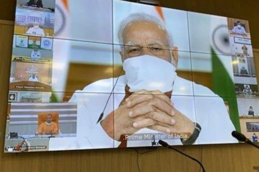 Wearing a mask, Prime Minister Narendra Modi holds a virtual meeting with chief ministers on Saturday.